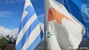 A blue-and-white Greek flag stands beside a mostly-white Cypriot flag (Photo: DW/V. Izotov)