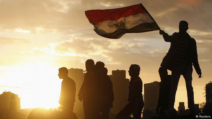 With a dramatic sunset backdrop illumating the scene from behind, a protestor stands on a ledge above his friends and waves the red, white and black Egyptian flag through the sunlight. (Photo: REUTERS/Mohamed Abd El Ghany)