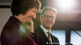 German Foreign Minister Guido Westerwelle, right, and Catherine Ashton, EU High Representative for Foreign Affairs and Security, left, smile during a news conference in Berlin, Germany, Friday, Feb. 1, 2013. Lens flares are pictured from a spotlight. (AP Photo/Gero Breloer)
