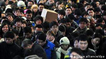 A crowd of Chinese passengers on their way back for the Spring Festival wait for trains at the Qingdao Railway Station in Qingdao city, east Chinas Shandong province, 26 January 2013.