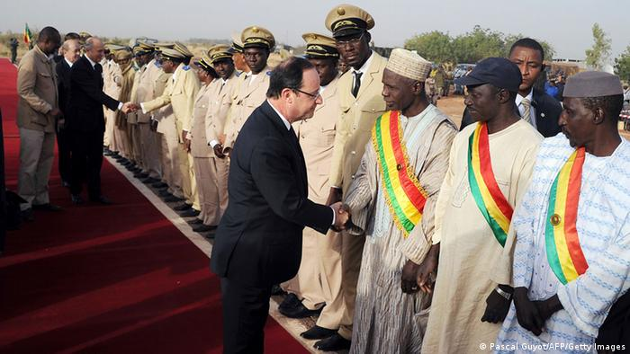 France's President Francois Hollande (C), flanked by French Foreign Affairs Minister Laurent Fabius (Back-3rdL) and French Defence Minister Jean-Yves Le Drian (Back-2ndL) shakes hands with Prefects of Mopti upon his arrival at Sevare, near Mopti, on February 2, 2013. President Francois Hollande visits Mali as French-led troops work to secure the last Islamist stronghold in the north after a lightning offensive against the extremists. Hollande will head to Timbucktu and Bamako. AFP