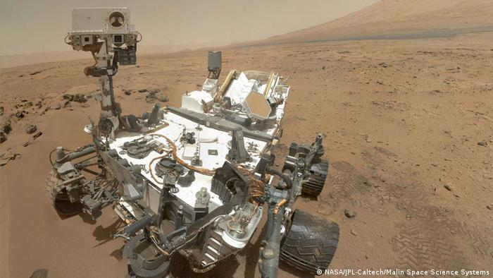 Auf dem Bild: High-Resolution Self-Portrait by Curiosity Rover Arm Camera On Sol 84 (Oct. 31, 2012), NASA's Curiosity rover used the Mars Hand Lens Imager (MAHLI) to capture this set of 55 high-resolution images, which were stitched together to create this full-color self-portrait. The mosaic shows the rover at Rocknest, the spot in Gale Crater where the mission's first scoop sampling took place. Four scoop scars can be seen in the regolith in front of the rover. The base of Gale Crater's 3-mile-high (5-kilometer) sedimentary mountain, Mount Sharp, rises on the right side of the frame. Mountains in the background to the left are the northern wall of Gale Crater. The Martian landscape appears inverted within the round, reflective ChemCam instrument at the top of the rover's mast. Self-portraits like this one document the state of the rover and allow mission engineers to track changes over time, such as dust accumulation and wheel wear. Due to its location on the end of the robotic arm, only MAHLI (among the rover's 17 cameras) is able to image some parts of the craft, including the port-side wheels. This high-resolution mosaic is a more detailed version of the low-resolution version created with thumbnail images, at: http://photojournal.jpl.nasa.gov/catalog/PIA16238 . Image Credit: NASA/JPL-Caltech/Malin Space Science Systems Quelle: http://marsprogram.jpl.nasa.gov/msl/multimedia/images/?ImageID=4845