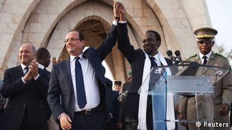 France's President Francois Hollande (2nd L) joins hands with Mali's interim president Dioncounda Traore in Bamako, Mali February 2, 2013.)