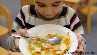 Ein Schulkind isst Gemüseeintopf (Foto: DPA)
