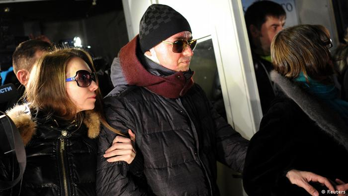 Sergei Filin (C), artistic director of Russia's Bolshoi Ballet, leaves a hospital accompanied by his wife Maria (L) in Moscow February 4, 2013. Filin was quoted on Sunday as saying he knew who was behind an attack on him in which a masked assailant splashed acid over his face threatening his eyesight. REUTERS/Vselovod Kutznestov (RUSSIA - Tags: ENTERTAINMENT CRIME LAW HEALTH)