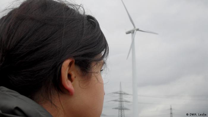 A resident of Cologne looks at a nearby wind turbine in her neighbourhood. (Copyright: DW/Andre Leslie February, 2013)