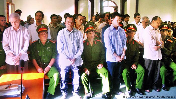 This picture taken on January 28, 2013 shows the ring leader Phan Van Thu (R-standing) and his group members standing trial at a local People's Court in the southern central province of Phu Yen. Vietnam on February 4 sentenced 22 activists to lengthy jail terms ranging from 10 years to life imprisonment, a defence lawyer said, in one of the country's largest subversion trials for years. Ring leader Phan Van Thu from the group called Hoi Dong Cong Luat Cong An Bia Son in Vietnamese, was given a life-long jail term while his 21 other members were handed between 10 and 17 years, according to the lawyer. AFP PHOTO / Vietnam News Agency (Photo credit should read Vietnam News Agency/AFP/Getty Images)
