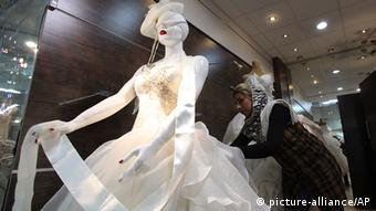 Iranian female shopkeeper adjusts a bridal gown (Photo: AP Photo/Vahid Salemi)