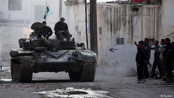 Free Syrian Army fighters ride on a tank outside a Syrian Army base during heavy fighting in the Arabeen neighbourhood of Damascus February 3, 2013. REUTERS/Goran Tomasevic (SYRIA - Tags: CIVIL UNREST POLITICS)