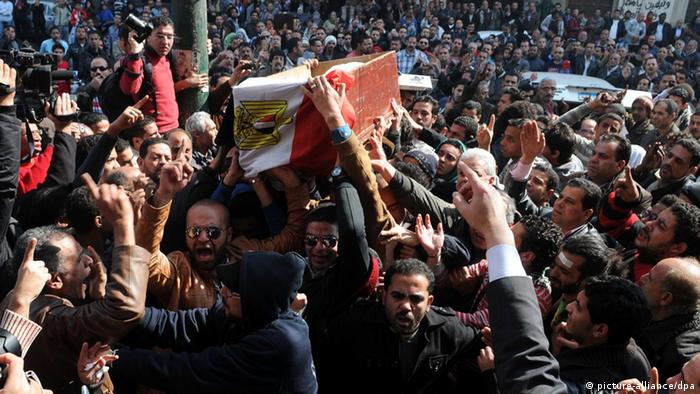 Egyptian mourners carry the coffin of one of the activists allegedly killed in recent clashes, Mohamed el Gindy, during their funeral in Cairo, Egypt, 04 February 2013. Photo: epa03568210 EPA/AHMED SADA