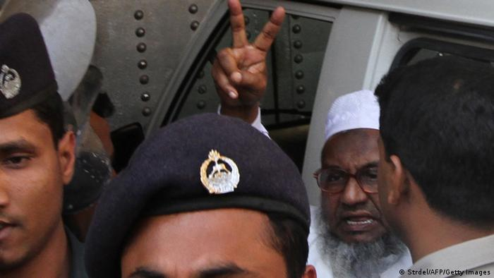 Abdul Quader Molla, 64, the fourth-highest ranked leader of the Jamaat-e-Islami party, gestures at the central jail in Dhaka on February 5, 2013. A Bangladeshi court sentenced a senior Islamist opposition official to life in prison Tuesday for mass murder and crimes against humanity during the 1971 liberation war against Pakistan. AFP PHOTO/STR (Photo credit should read STRDEL/AFP/Getty Images)