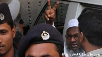 Abdul Quader Molla, 64, the fourth-highest ranked leader of the Jamaat-e-Islami party, gestures at the central jail in Dhaka on February 5, 2013 (Photo: STRDEL/AFP/Getty Images)