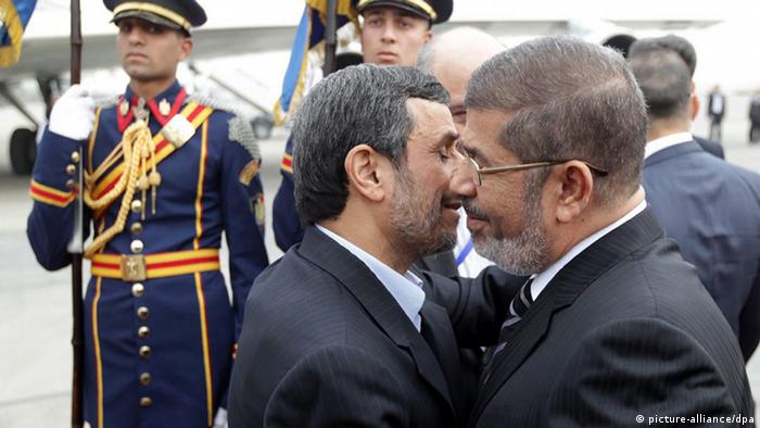 epa03569099 A handout picture made available by Iranian President Mahmoud Ahmadinejad's official website shows Egyptian President Mohamed Morsi (R) greeting President Ahmadinejad (2-R) at the airport in Cairo, Egypt, 05 February 2013. Ahmadinejad arrived in Cairo in the first visit by an Iranian head of state to Egypt in more than 30 years. He is leading the Iranian delegation to a summit of the Organization of Islamic Cooperation, which starts in the Egyptian capital on 06 February. EPA/AHMADINEJAD OFFICIAL WEBSITE HAN HANDOUT EDITORIAL USE ONLY/NO SALES