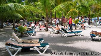 People lie on deck chairs on a sandy beach (Foto: CC BY-SA 2.0: Ronald Saunders)