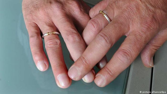 A close-up photo of two men's hands, with wedding rings, touching. (Photo: Julian Stratenschulte dpa)