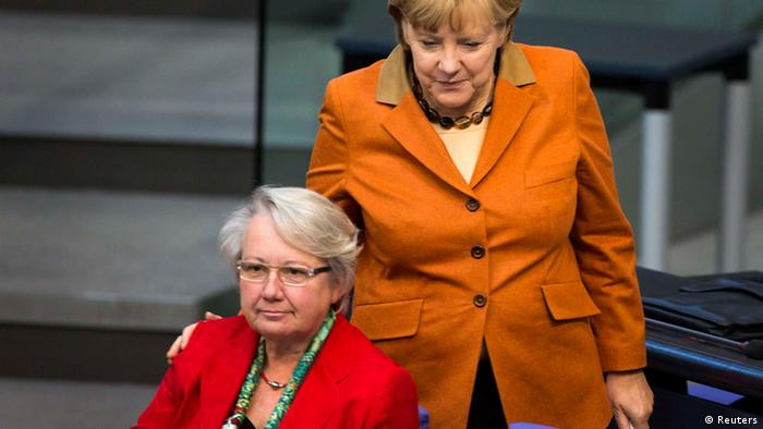 File picture shows German Chancellor Angela Merkel (L) as she puts her hands on the shoulder of Education Minister Annette Schavan during a session of the Bundestag, the German lower house of parliament, in Berlin October 18, 2012. Chancellor Angela Merkel's education minister was stripped of her doctorate on February 6, 2013 for alleged plagiarism in her work, a move that could embarrass the German leader as she seeks election to a third term in office. Picture taken October 18, 2012. REUTERS/Thomas Peter/File (GERMANY - Tags: POLITICS)