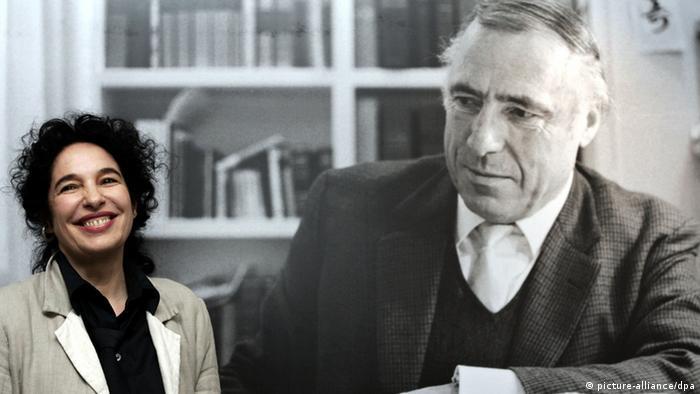 Ulla Unseld-Berkewicz smiles next to large photo of Siegfried Unseld