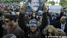Tunisian protesters shout slogans during a rally outside the Interior Ministry to protest against the assassination of Tunisian opposition leader and outspoken government critic Chokri Belaid (poster) on February 6, 2013, in Tunis. The protesters, who massed on Habib Bourguiba Avenue, epicentre of the 2011 uprising that ousted former dictator Zine El Abidine Ben Ali, pelted the police with bottles and the police responded by firing tear gas, chasing the protesters and beating them with batons. AFP PHOTO / FETHI BELAID (Photo credit should read FETHI BELAID/AFP/Getty Images)