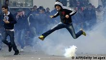 A Tunisian protester jumps amid smoke after police fired tear gas during a rallye outside the Interior ministry to protest after Tunisian opposition leader and outspoken government critic Chokri Belaid was shot dead with three bullets fired from close range, on February 6, 2013 in Tunis. The protesters, who massed on Habib Bourguiba Avenue, epicentre of the 2011 uprising that ousted ex-dictator Zine El Abidine Ben Ali, pelted the police with bottles and the police responded by firing tear gas, chasing the protesters and beating them with batons. AFP PHOTO / FETHI BELAID (Photo credit should read FETHI BELAID/AFP/Getty Images)