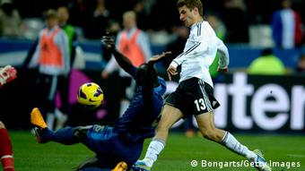 Thomas Müller of Germany scores under the pressure of Mamadou Cabaye (Photo: Dennis Grombkowski/Bongarts/Getty Images)