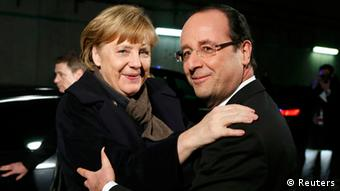 France's President Francois Hollande (R) welcomes German Chancellor Angela Merkel at the Stade de France in Saint-Denis, near Paris, before attending a friendly international soccer match between France and Germany, February 6, 2013. REUTERS/Patrick Kovarik/Pool (FRANCE - Tags: POLITICS SPORT SOCCER)