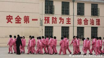 --FILE--A Chinese police officer escorts inmates at a female labor camp in Jurong city, east Chinas Jiangsu province, 6 March 2008. Meng Jianzhu, who became secretary of the Political and Legal Affairs Committee in November, said at a national law and order work conference that the re-education through labour, or laojiao, system would be halted after the move was rubber-stamped by the National Peoples Congress in March. The remarks were first reported by the bureau chief of the Legal Daily, the Justice Ministrys official mouthpiece, and were picked up by state media outlets. An official who attended the event confirmed Mengs comments. But state media sent mixed signals about the policy. A Xinhua report on the conference said only that authorities had pledged to reform the system, and some analysts noted that Meng spoke of halting rather than abolishing the laojiao system. pixel
