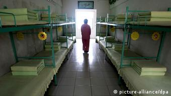 --FILE--A Chinese inmate walks past beds in a room at a female labor camp in Jurong city, east Chinas Jiangsu province, 6 March 2008. Meng Jianzhu, who became secretary of the Political and Legal Affairs Committee in November, said at a national law and order work conference that the re-education through labour, or laojiao, system would be halted after the move was rubber-stamped by the National Peoples Congress in March. The remarks were first reported by the bureau chief of the Legal Daily, the Justice Ministrys official mouthpiece, and were picked up by state media outlets. An official who attended the event confirmed Mengs comments. But state media sent mixed signals about the policy. A Xinhua report on the conference said only that authorities had pledged to reform the system, and some analysts noted that Meng spoke of halting rather than abolishing the laojiao system. pixel