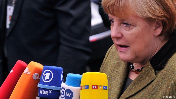 Merkel spricht in Mikrophone Photo: Reuters