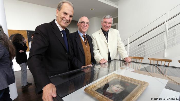 Представители ЮНИСЕФ, музея Ханса Арпа и земельного правительства Рейнланд-Пфальца с картиной Ренуара Femme a la rose из колекции Густава Рау.