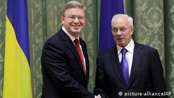 European Commissioner for Enlargement and European Neighborhood Policy Stefan Fuele, left, shakes hands with Ukraine Prime Minister Mykola Azarov during their meeting in Kiev, Ukraine, Thursday, Feb. 7, 2013. (AP Photo/Sergei Chuzavkov)