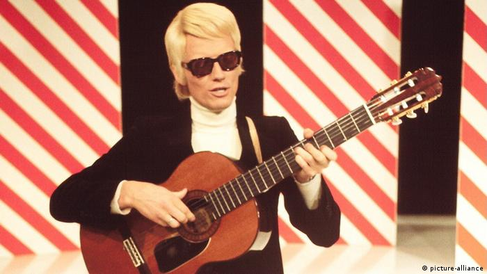 blonde man wearing dark sunglasses plays a guitar on stage
