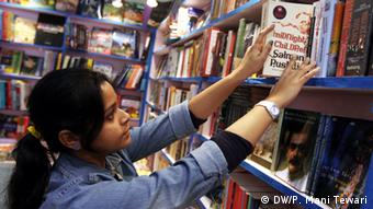 A young booklover searching through the collections in a stall in Kolkata Book Fair in January 2013