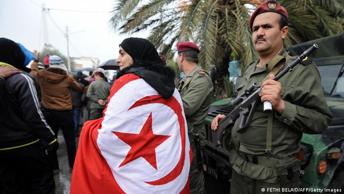 A woman wearing a national flag walks past a Tunisian soldier standing guard during late opposition leader Chokri Belaid's funeral procession which makes its way to the nearby cemetery of El-Jellaz where Belaid is to be buried on February 8, 2013 in the Djebel Jelloud district, a suburb of Tunis. Thousands of people attend the funeral while Tunis is at a near standstill, with streets deserted, shops shut and public transport at a minimum as a general strike called by a powerful trade union after Bellaid was murdered took effect. AFP PHOTO / FETHI BELAID (Photo credit should read FETHI BELAID/AFP/Getty Images)