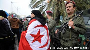 A woman wearing a national flag (Photo: FETHI BELAID/AFP/Getty Images)