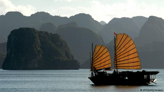 A tourist boat sails past the stone islands of Halong Bay, 08 July 2007. (Photo: PHILIPPE LOPEZ/AFP/Getty Images)