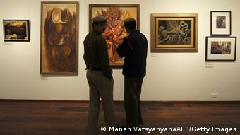 Indian policemen look at paintings during an art exhibition The Naked and the Nude (Photo: AFP PHOTO/ MANAN VATSYAYANA)