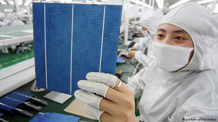 Photo: A Chinese woman examines a solar cell (Foto: Xu Ruiping/Imaginechina)