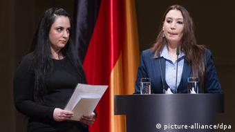 Semiya Simsek (r) and another young, female family member of NSU victims stand at a podium in front of the German flag at a memorial in Berlin. (Photo: Michael Kappeler dpa/lbn)