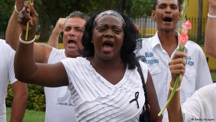The new leader of the Cuban opposition group Ladies in White, Berta Soler (C), chants slogans during a march in memory of their late leader Laura Pollan, on October 16, 2011 in front of Santa Rita's Church in Havana. Pollan, founder of Cuba's Ladies in White dissident group, died Friday in a Havana hospital aged 63, fellow activists said, hailing her work and lamenting the loss to the opposition's cause. AFP PHOTO/CARLOS BATISTA (Photo credit should read CARLOS BATISTA/AFP/Getty Images)
