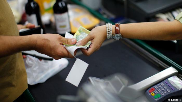 Caixa de supermercado em Caracas recebe pagamento de cliente