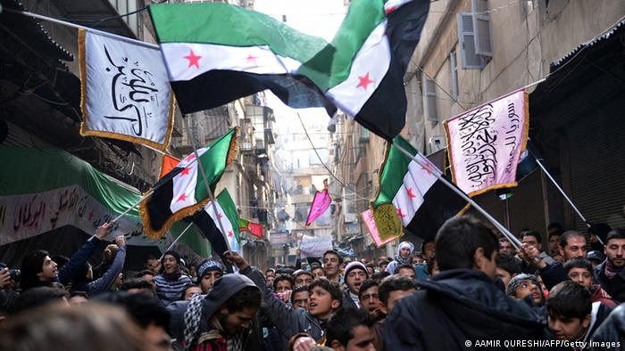 Syrian anti-regime protesters wave pre-Baath Syrian flags, now used by the Free Syrian Army, during a demonstration after the weekly Friday prayers in the Bustan al-Qasr district of the northern city of Aleppo on February 8, 2013. Syrian forces shelled rebel belts, the Syrian Observatory for Human Rights said, as an army offensive raged into a third straight day. AFP PHOTO/AAMIR QURESHI (Photo credit should read AAMIR QURESHI/AFP/Getty Images)