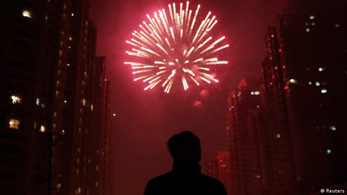 A man watches as fireworks light up the skyline of Shanghai in celebration of Chinese New Year in Shanghai early February 10, 2013. The Lunar New Year, or Spring Festival, begins on February 10 and marks the start of the Year of the Snake, according to the Chinese zodiac. REUTERS/Carlos Barria (CHINA - Tags: SOCIETY)