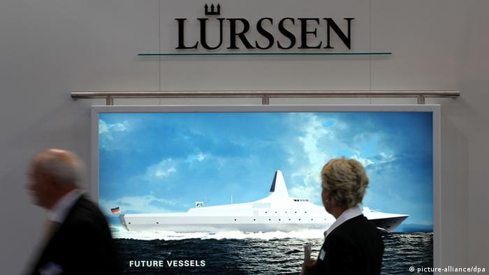 People looking at poster of Lürssen ship (Photo: Christian Charisius/dpa)