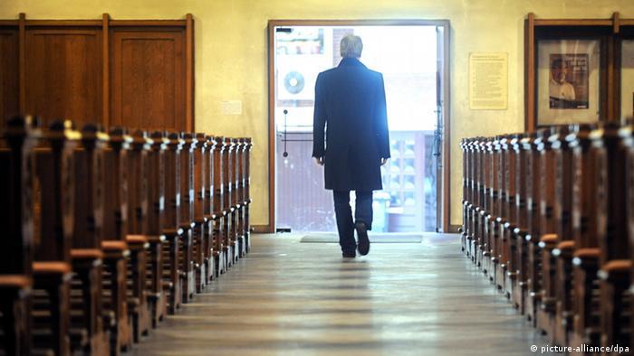 Mann läuft zwischen Kirchenbänken hindurch in Richtung Ausgang - Foto: picture-alliance/dpa