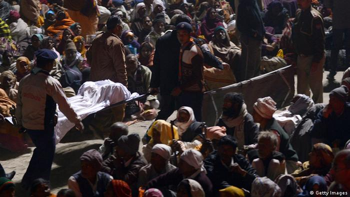 Indian authorities carry the bodies of two travellers killed in a stampede at the railway station in Allahabad on February 10, 2013. At least 10 people died in the stampede as pilgrims headed home from India's giant Kumbh Mela festival, which drew a record 30 million people to the banks of the river Ganges. Dozens more were injured in the crush and some local television channels put the death toll as high as 20. Local officials said that the railings on a bridge at Allahabad station had given way under the pressure of the mass of people, while eyewitnesses told local media that the police had baton-charged the crowd leading to panic. AFP PHOTO/ ROBERTO SCHMIDT (Photo credit should read ROBERTO SCHMIDT/AFP/Getty Images)