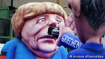 A Carnival float in Düsseldorf shows a depiction of Angela Merkel's face, with a Greek caricature using a giant pencil to paint on a Hitler moustache, on February 11, 2013. (Photo: Martin Gerten/dpa)