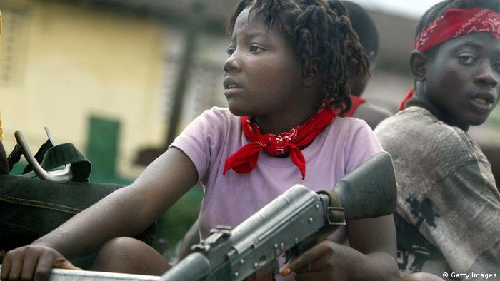 A girl soldier sits in a truck (Photo: Chris Hondros)