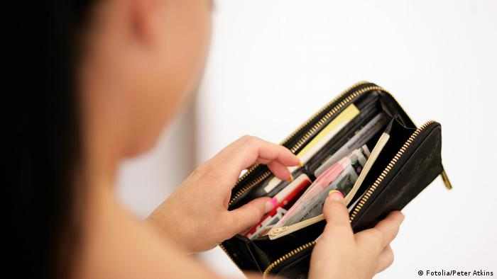 Woman looking through wallet