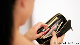 Женщина смотрит в кошелек