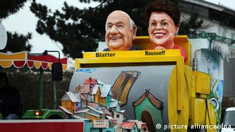 A Carnival float in Colonge, on 11.02.2013, showing Sepp Blatter and Dilma Rousseff at the wheel of a bulldozer, crushing a settlement. (Photo: Oliver Berg/dpa)